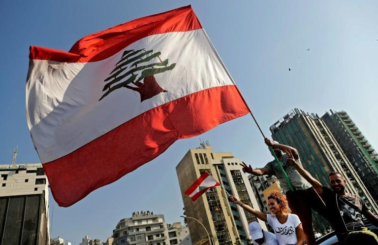 Protesters hold up a Lebanese flag outside Beirut's port, on the first anniversary of the blast that destroyed swathes of the capital