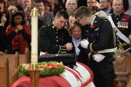 Kathy Cirillo is comforted in front of the coffin of her son Cpl. Nathan Cirillo at his regimental funeral service in Hamilton, Ontario October 28, 2014. REUTERS/Nathan Denette/Pool