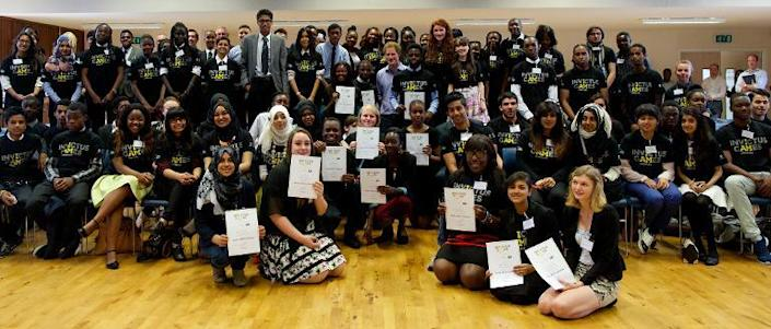 Britain's Prince Harry (C) visits Bethnal Green Academy in London on July 21, 2014, where he joined a group of 60 students from schools across east London who will be receiving training to become digital media champions for the Invictus Games (AFP Photo/Andrew Cowie)