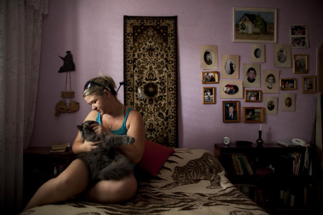In this July. 6, 2012 photo, Alexandra Bahman, who emigrated to Israel from Moldova in 2006, sits in her bedroom with her cat. Bahman left Moldova with the carpet and photos that now decorate her bedroom walls, in Ashdod, Israel. Ashdod is heavily populated by immigrants from the former Soviet Union. (AP Photo/Oded Balilty)