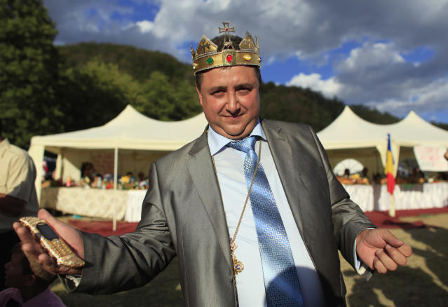 Self proclaimed international king of gypsies Dan Stanescu gestures with his golden plated mobile phone in hand during the traditional ethnic Roma festival in Costesti, 210 km (128 miles) west of Bucharest, September 8, 2012. Following their tradition, thousands of Roma from all over Romania, which has Europe's largest Roma community, gather every year to celebrate the birthday of St. Mary, to make wedding arrangements for their sons and daughters and to show off their wealth. REUTERS/Radu Sigheti (ROMANIA - Tags: SOCIETY RELIGION)