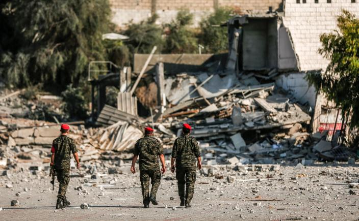 <p>TOPSHOT – Members of Hamas' military police walk through a site that was hit by Israeli airstrikes in Gaza City on Aug. 9, 2018. (Photo: Mahmud Hams/AFP/Getty Images) </p>