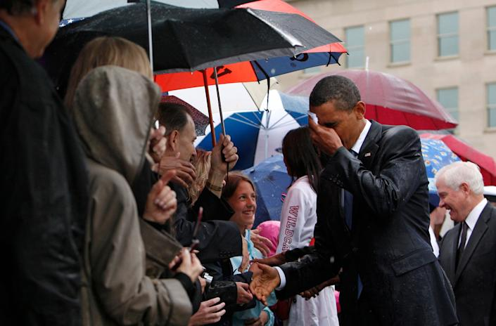 Barack Obama wipes the rain off his face as he meets Pentagon staff and family members of the victims of the September 11 attacks in a ceremony marking the eighth anniversary of the tragedy at the Pentagon in 2009. (Photo: Jim Young / Reuters)