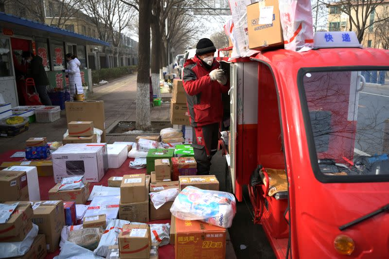 FILE PHOTO: A JD.com delivery worker wearing a face mask unloads parcels outside a residential compound, as the country is hit by an outbreak of the novel coronavirus, in Beijing