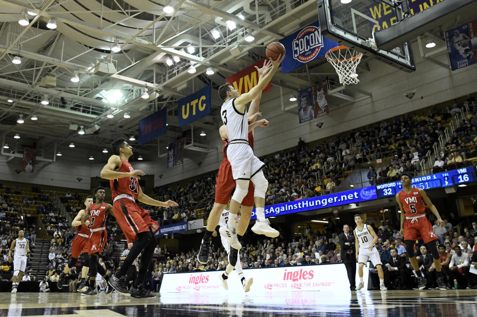 Wofford Fletcher Magee (3) drives the ball to the basket past VMI guard Sarju Patel (31), forward Tyler Creammer, (behind Magee) and guard Greg Parham (5) in the first half of an NCAA college basketball game for the Southern Conference basketball tournament championship, Saturday, March 9, 2018, in Asheville, N.C. Wofford won 97-72. (AP Photo/Kathy Kmonicek