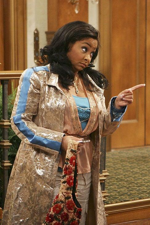 Raven in a shiny flower-pattern coat with satin stripes down the sleeves, khaki bermuda shorts, an embroidered flower bag, a tank with a sequin heart on it, and a satin deep v peplum top with sequin trim on the neckline
