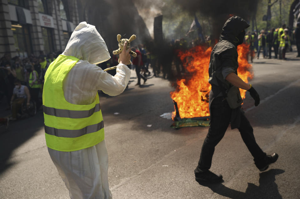Two protestors walk by a pile of wood burning in the street during a yellow vest demonstration in Paris, Saturday, April 20, 2019. French yellow vest protesters are marching anew to remind the government that rebuilding the fire-ravaged Notre Dame Cathedral isn't the only problem the nation needs to solve. (AP Photo/Francisco Seco)