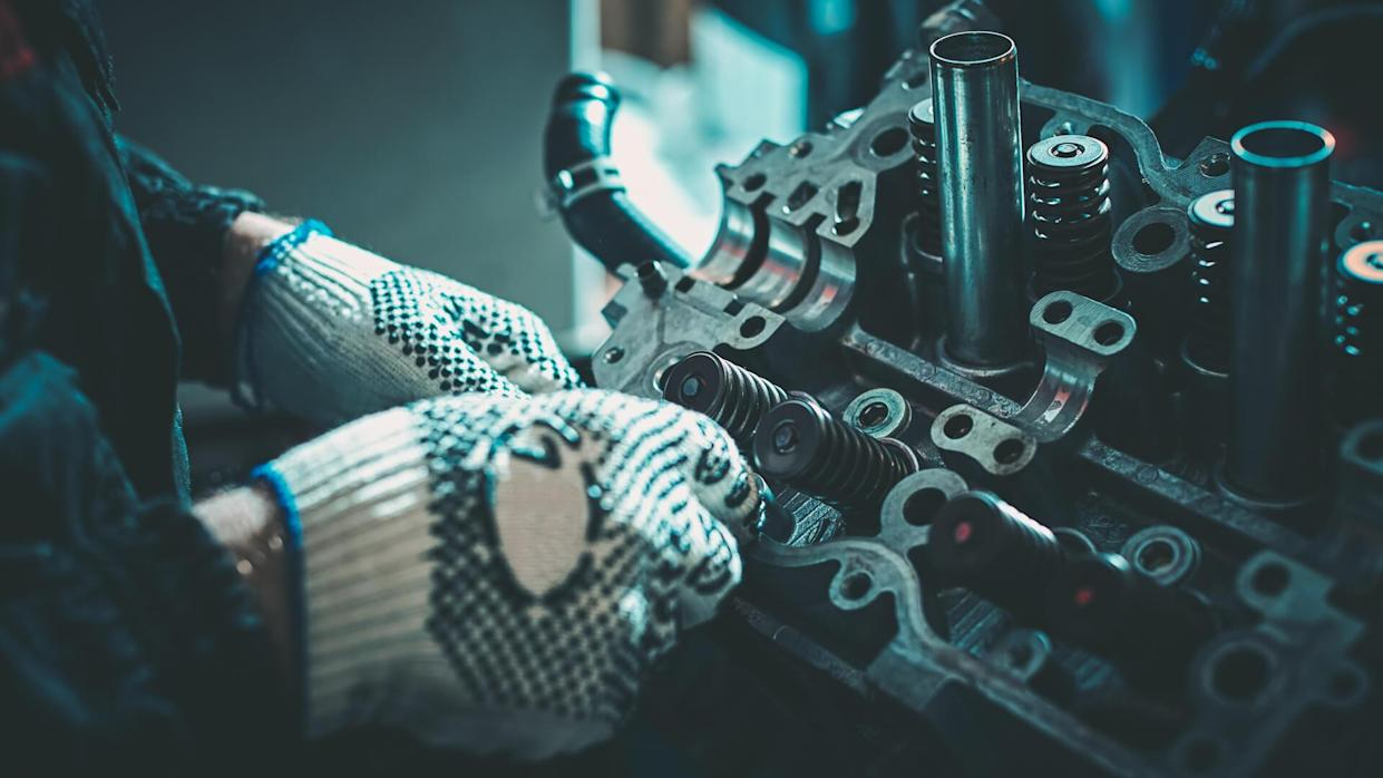 The auto mechanic deconstructs the internal combustion engine for diagnosis and repair.