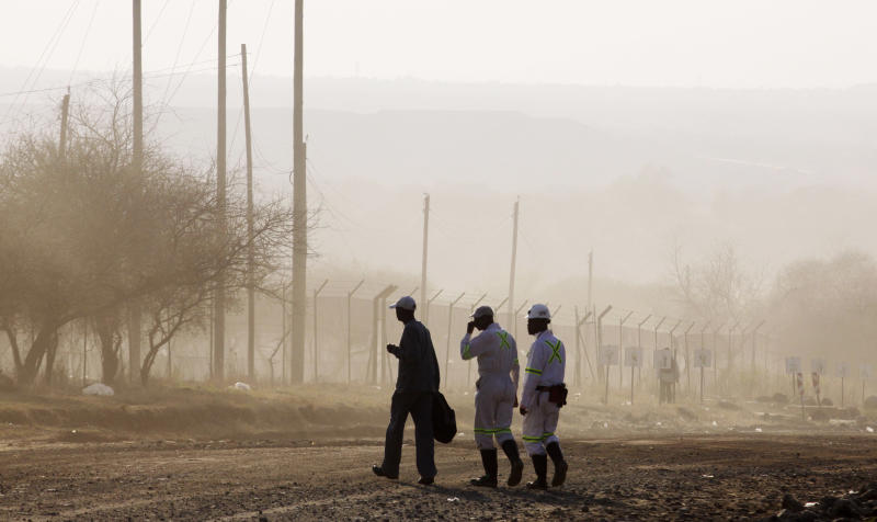 Miners return to work at the Lonmin Platinum mine after Lonmin resolved a five-week strike by agreeing to pay raises of up to 22 percent, in Marikana, Rustenburg, South Africa, Thursday, Sept. 20, 2012. (AP Photo/Denis Farrell)