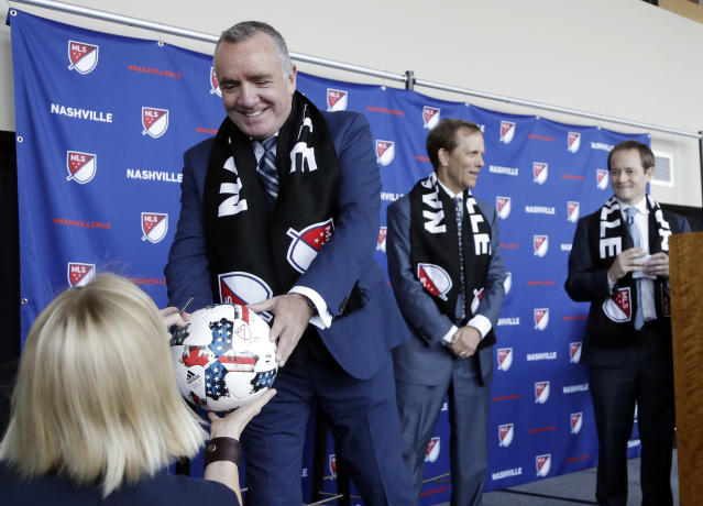 Ian Ayre, left, hands over a soccer ball after posing for pictures at a news conference where he was introduced as the first chief executive officer of the Nashville MLS franchise Monday, May 21, 2018, in Nashville, Tenn. Ayre is a former CEO of Liverpool Football Club of the English Premier League. (AP Photo/Mark Humphrey)