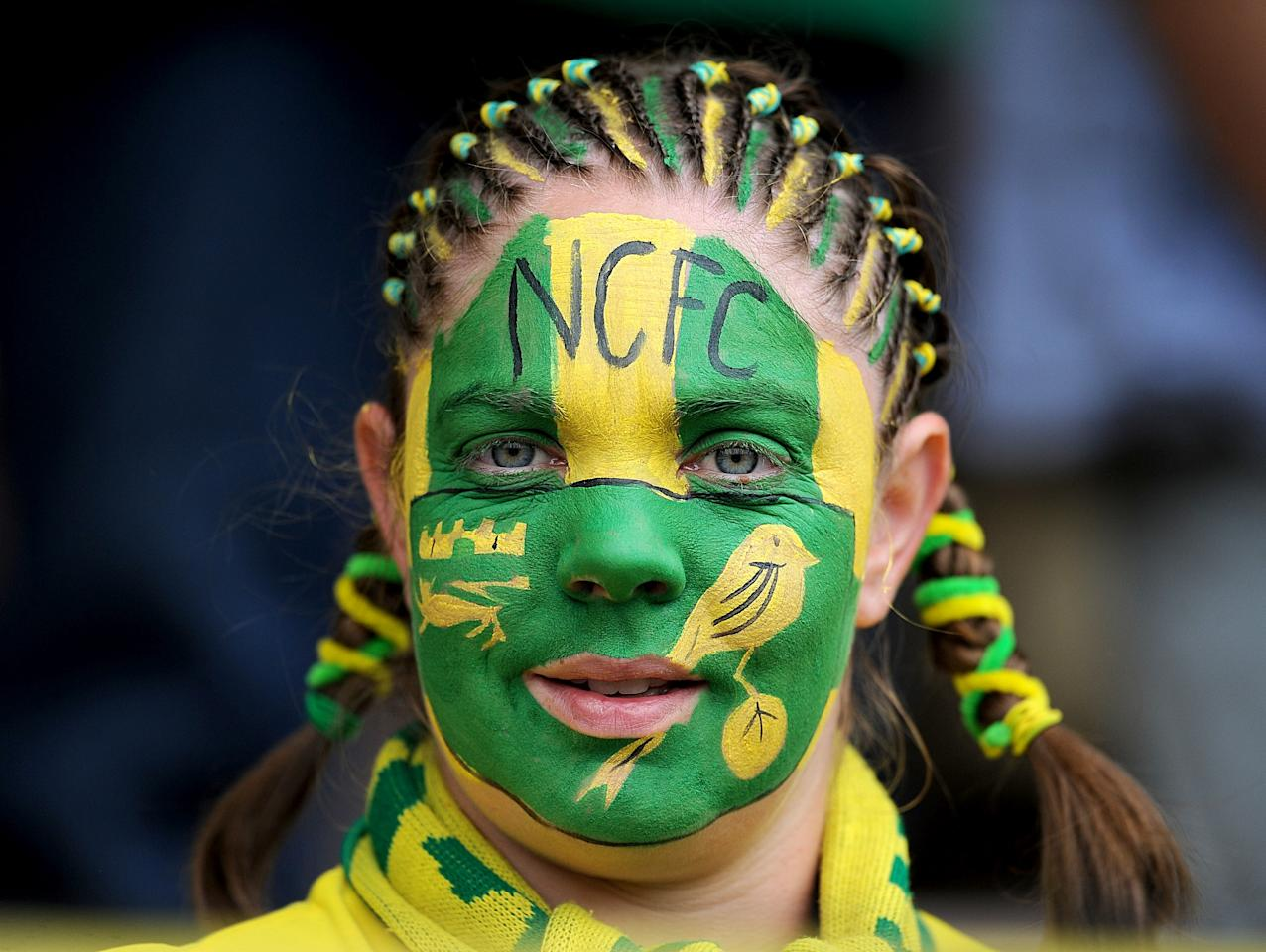 A Norwich City fan shows off her facepaint in the stands before kick-off