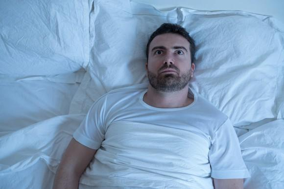 Very worried person laying in bed with eyes open, unable to sleep.