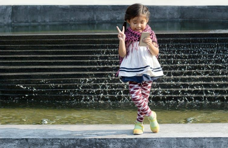 Young girl looking at her smartphone and making peace sign.