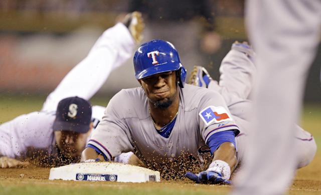 Texas Rangers' Elvis Andrus, right, dives back to first after being caught in a run-down as Seattle Mariners shortstop Willie Bloomquist dives behind on a tag in the seventh inning of a baseball game Saturday, June 14, 2014, in Seattle. Andrus was first called out, but the call was overturned to safe after a review. (AP Photo/Elaine Thompson)