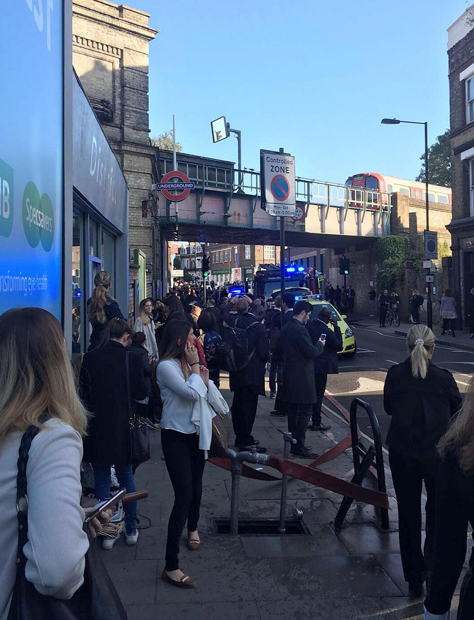 <p>Shocked pedestrians look on near the exit of Parsons Green station as news of the blast emerged. (PA) </p>