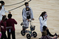Injured South Carolina guard LeLe Grissett, center, uses a scooter during a timeout in the second half of a college basketball game against Georgia Tech in the Sweet Sixteen round of the women's NCAA tournament at the Alamodome in San Antonio, Sunday, March 28, 2021. (AP Photo/Eric Gay)
