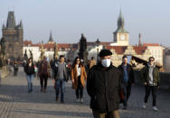 A man wearing a face mask walks across the medieval Charles Bridge in Prague, Czech Republic, Thursday, Feb. 25, 2021. The Czech government is barring the citizens and residents from travelling to the countries hit by highly contagious coronavirus variants and is tightening the rules for face coverings. Starting on Thursday, the Czechs are required to wear better masks in places where large numbers gather, including stores, hospitals and public transportation. (AP Photo/Petr David Josek)