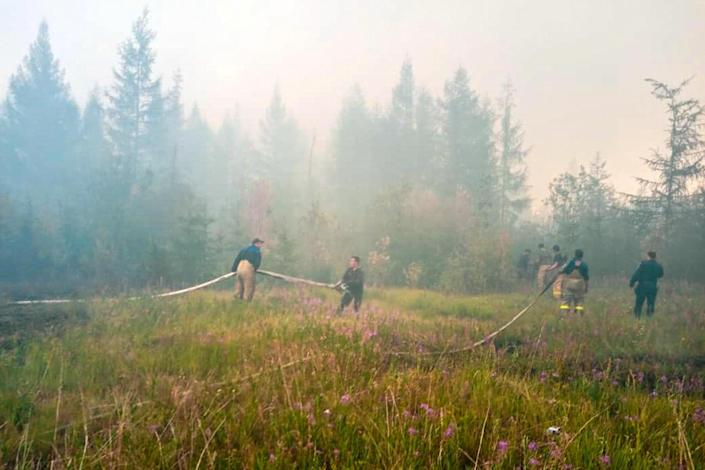 Firefighters work to extinguish forest fires near the village of Batagay, Sakha Republic, also called Yakutia, in Russia's Siberia region. Freakishly warm weather and dry conditions across large swathes of Siberia have contributed to a resurgence of wildfires in the summer of 2020. / Credit: RUSSIAN EMERGENCY MINISTRY/AFP via Getty Images