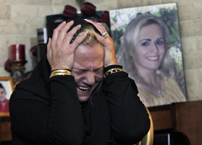 In this Tuesday, March 4, 2014 photo, Nada Sabbagh, weeps in front of a picture of her daughter Manal Assi, who was killed last month, as she recounts during an interview with The Associated Press, how her son-in-law killed her daughter in front of family members, south of Beirut, Lebanon. The killing of Sabbagh's daughter is one of three domestic violence slayings in Lebanon in recent months, drawing new attention to women's rights in this country of 4 million people. Although Lebanon appears very progressive on women rights compared to other countries in the Middle East, domestic violence remains an unspoken problem and the nation's parliament has yet to vote on a bill protecting women's rights nearly three years after it was approved by the Cabinet. (AP Photo/Bilal Hussein)