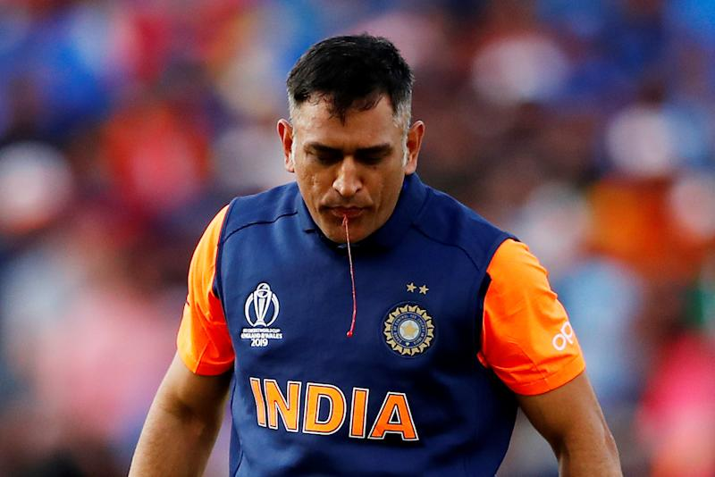 Cricket - ICC Cricket World Cup - England v India - Edgbaston, Birmingham, Britain - June 30, 2019 India's MS Dhoni spits out blood after sucking his cut thumb Action Images via Reuters/Andrew Boyers