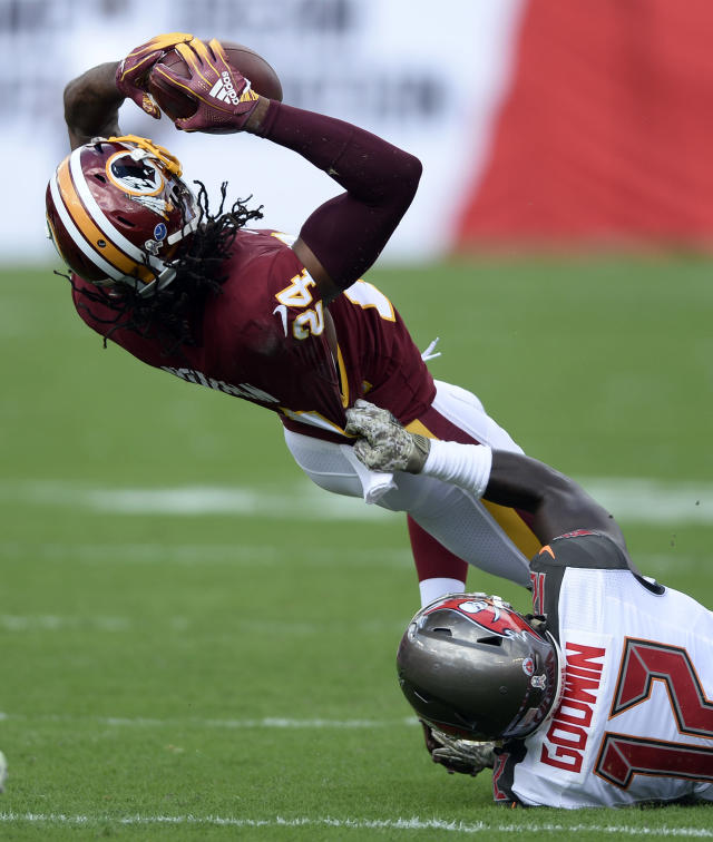 Washington Redskins cornerback Josh Norman (24) interecpts a pass by Tampa Bay Buccaneers' Ryan Fitzpatrick (14) intended for wide receiver Chris Godwin (12) during the first half of an NFL football game Sunday, Nov. 11, 2018, in Tampa, Fla. (AP Photo/Jason Behnken)