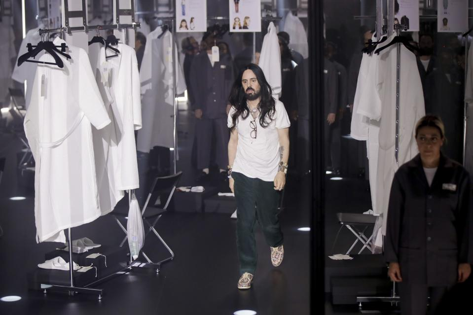 FILE - In this Wednesday, Feb. 19, 2020 file photo, Designer Alessandro Michele walks out at the end of Gucci's Fall/Winter 2020/2021 collection, presented in Milan, Italy. Gucci and St. Laurent are two of the highest profile luxury fashion houses to announce they will leave the fashion calendar behind, with its relentless four-times-a-year rhythm, shuttling cadres of fashionistas between global capitals where they squeeze shoulder-to-shoulder around runways for 15 breathless minutes. (AP Photo/Luca Bruno, File)