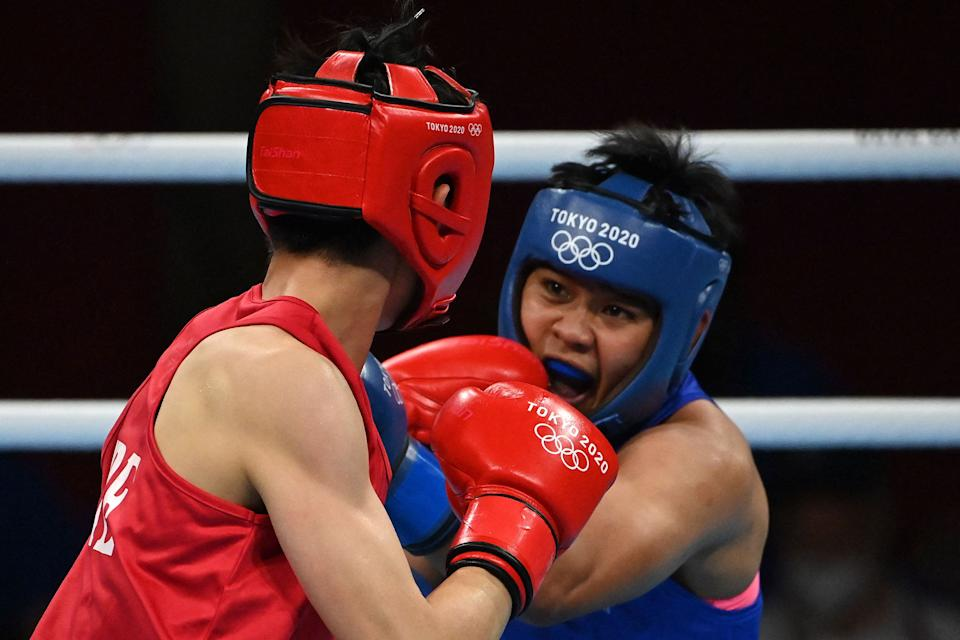 Chinese Taipei's Yu-Ting Lin (red) and Philippines' Nesthy Petecio fight during their women's feather (54-57kg) preliminaries round of 16 boxing match during the Tokyo 2020 Olympic Games at the Kokugikan Arena in Tokyo on July 26, 2021. (Photo by Luis ROBAYO / AFP) (Photo by LUIS ROBAYO/AFP via Getty Images)