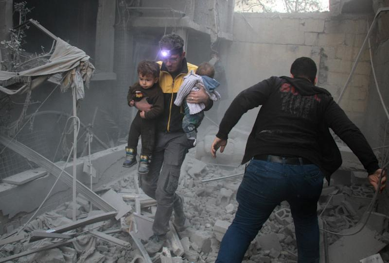 A Syrian man carries two children in the rubble of buildings following regime air strikes on the rebel-held besieged town of Douma in the eastern Ghouta region, on the outskirts of the capital Damascus (AFP Photo/Hamza Al-Ajweh)