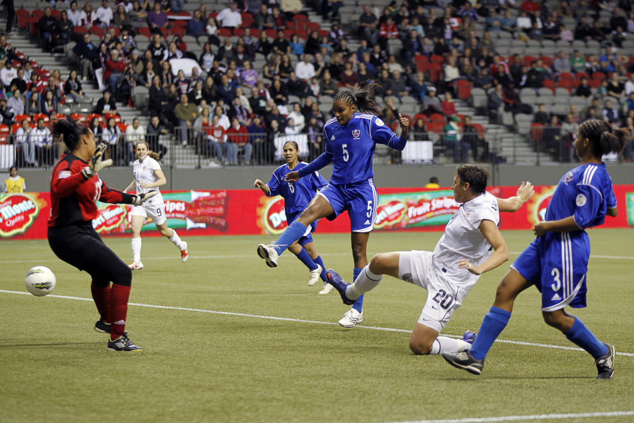 VANCOUVER, CANADA - JANUARY 20: Mary Abigail Wambach #20 of the United States scores against Heidy Salazar #12 of the Dominican Republic despite the defensive play of Denny Vargas #3 and Ana Diaz #5 of the Dominican Republic during their game at the 2012 CONCACAF Women's Olympic Qualifying Tournament at BC Place on January 20, 2012 in Vancouver, British Columbia, Canada.  (Photo by Jeff Vinnick/Getty Images)