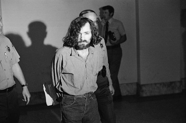 <p>Charles M. Manson, squinting in the glare of a film cameraman's floodlight, marches to court, Aug. 20, 1970, for a hearing on his claim that he is being mistreated by deputies in the Los Angeles County Jail. After the hearing, his trial on murder charges resulting from the slayings of actress Sharon Tate and six other people was scheduled to resume. (Photo: George Brich/AP) </p>