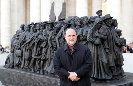 Sculptor Timothy P. Schmalz poses with his statue after Pope Francis held a Mass for the World Day of Migrants and Refugees at the Vatican