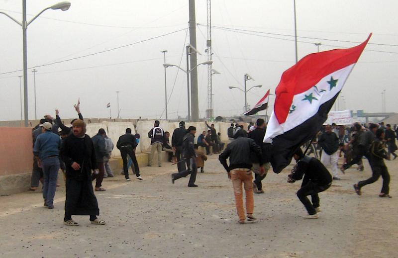 Protesters throw stones towards an Iraqi a checkpoint during clashes in Fallujah, 40 miles (65 kilometers) west of Baghdad, Iraq, Friday, Jan. 25, 2013. Iraqi troops shot dead five protesters Friday as they opened fire at stone-hurling demonstrators angry at the troops for preventing them from joining an anti-government rally west of Baghdad, officials said. (AP Photo/ Bilal Fawzi)