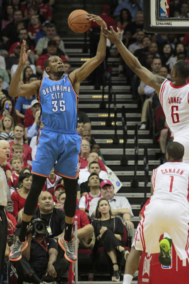 Oklahoma City Thunder forward Kevin Durant reaches for a rebound against Houston Rockets forward Terrence Jones, 6, during an NBA basketball game in Houston Friday, April 4, 2014. (AP Photo/Richard Carson)