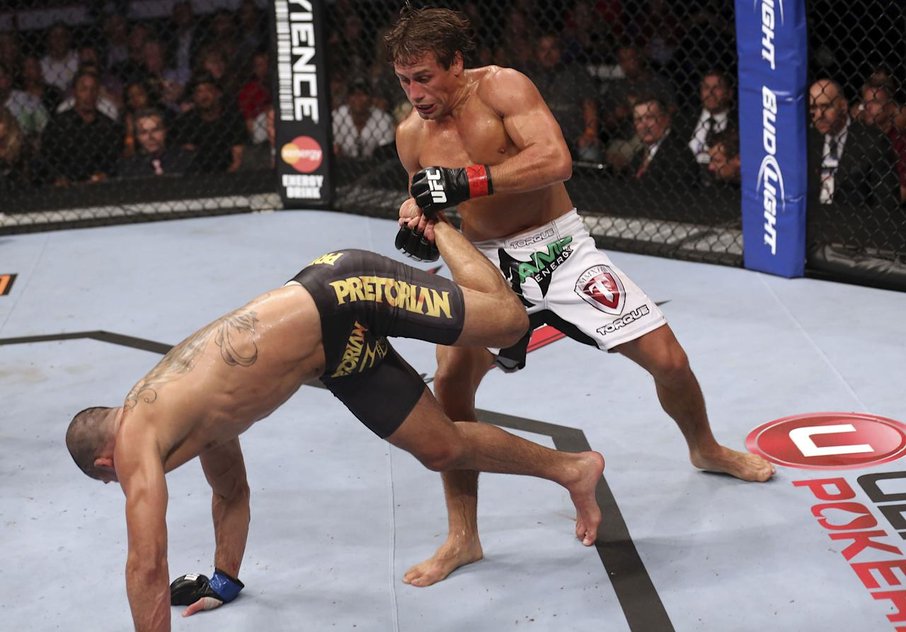 Urijah Faber counters a kick from Renan Barao during their UFC interim bantamweight championship bout at UFC 149 inside the Scotiabank Saddledome on July 21, 2012 in Calgary, Alberta, Canada. (Photo by Nick Laham/Zuffa LLC/Zuffa LLC via Getty Images)