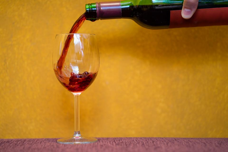 Red wine pouring in a glass on yellow background