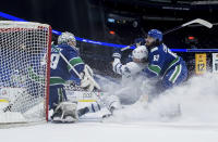 Toronto Maple Leafs' William Nylander (88) is hauled down by Vancouver Canucks' Jalen Chatfield (63) as goalie Braden Holtby (49) makes the save during the second period of an NHL hockey game in Vancouver, British Columbia, on Tuesday, April 20, 2021. (Darryl Dyck/The Canadian Press via AP)