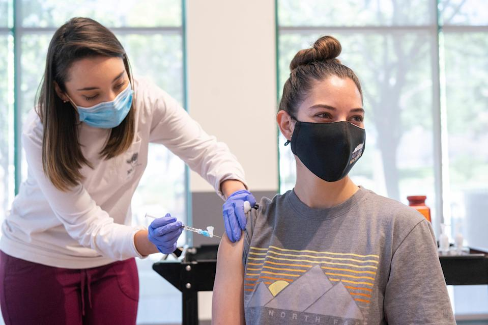 This photo provided by New Mexico State University shows Aggie Health and Wellness Center nurse Marissa Archuleta (left) administering a Johnson & Johnson COVID-19 vaccine to Lauren Naranjo at a walk-in clinic at Corbett Center in Las Cruces, New Mexico.