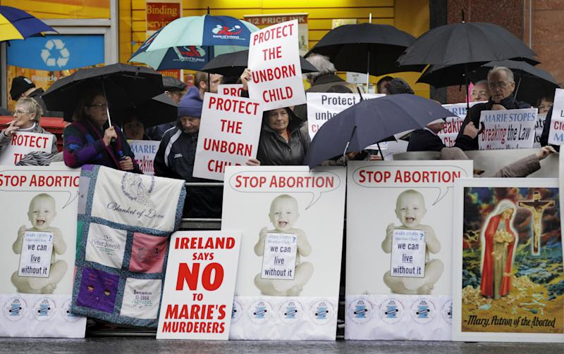 Protesters opposed to abortion hold placards outside the Marie Stopes clinic in Belfast, Northern Ireland, Thursday, 18, 2012. The first abortion clinic on the island of Ireland has opened in Belfast, sparking protests by Christian conservatives from both the Catholic and Protestant sides of Northern Ireland's divide.  The Marie Stopes center plans to offer the abortion pill to women less than nine weeks pregnant _ but only if doctors determine they're at risk of death or long-term health damage from their pregnancy.  That's the law in both Northern Ireland and the Republic of Ireland, where abortion is otherwise illegal.    (AP Photo/Peter Morrison)