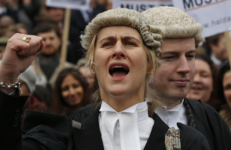Bewigged British lawyers march to protest fee cuts