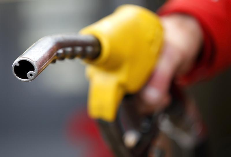 An attendant prepares to refuel a car at a petrol station in Rome