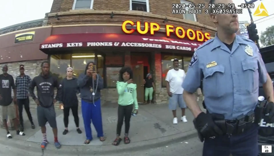 In this image from police body camera video former Minneapolis police Officer Derek Chauvin stands outside Cup Foods in Minneapolis, on May 25, 2020, with a crowd of onlookers behind him. The image was shown as prosecutor Steve Schleicher gave closing arguments as Hennepin County Judge Peter Cahill presided Monday, April 19, 2021, at the Hennepin County Courthouse in Minneapolis, in the trial of Chauvin who is charged in the May 25 death of George Floyd. (Court TV via AP, Pool)