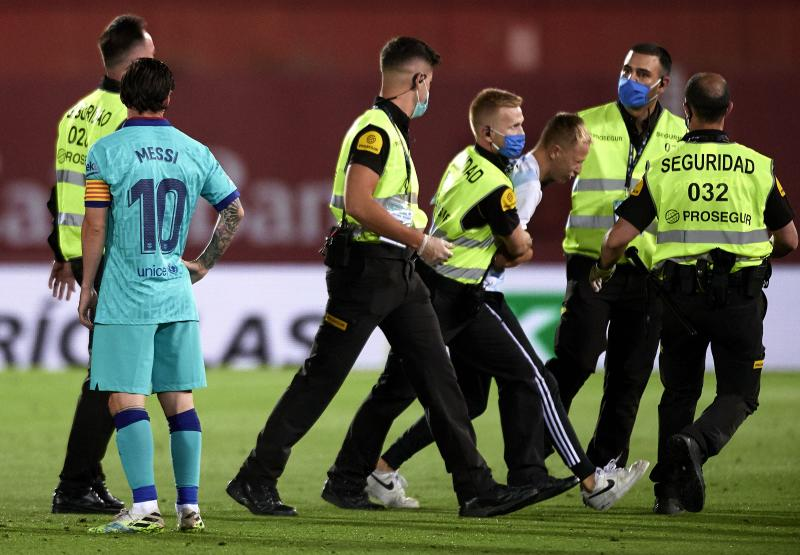 MALLORCA, SPAIN - JUNE 13: A pitch invader is escorted off the pitch during the Liga match between RCD Mallorca and FC Barcelona at Iberostar Estadi on June 13, 2020 in Mallorca, Spain. (Photo by Quality Sport Images/Getty Images)