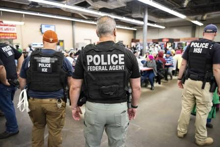 Officers from Immigration and Customs Enforcement (ICE) look on after executing search warrants and making some arrests at an agricultural processing facility in Canton
