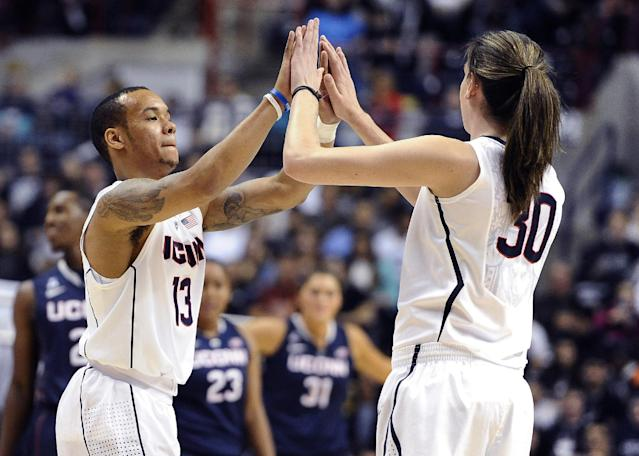 FILE - In this Friday, Oct. 18, 2013, file photo, Connecticut's Shabazz Napier, left, high-fives teammate Breanna Stewart during an inter-squad scrimmage at the men's and women's basketball teams' First Night event in Storrs, Conn. Connecticut's men's and women's teams are in the Final Four together for the fourth time. No other school has done it more than once. (AP Photo/Jessica Hill, File)