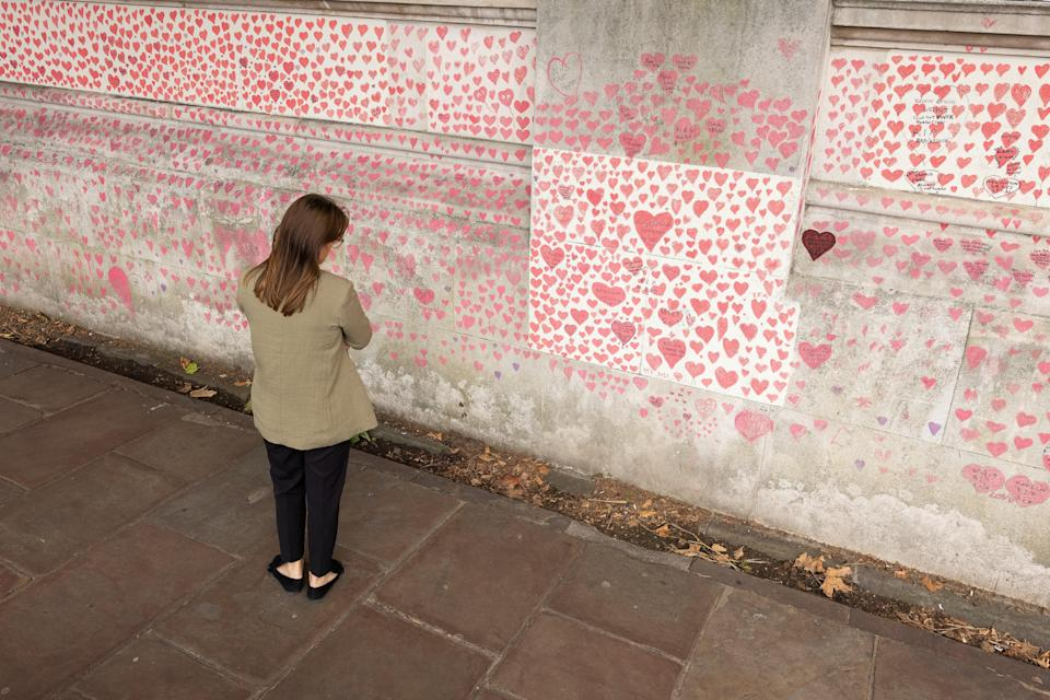 A woman pauses to look at the hearts and personal tributes to some of those lost to Covid-19 on a memorial wall in London (Getty Images)