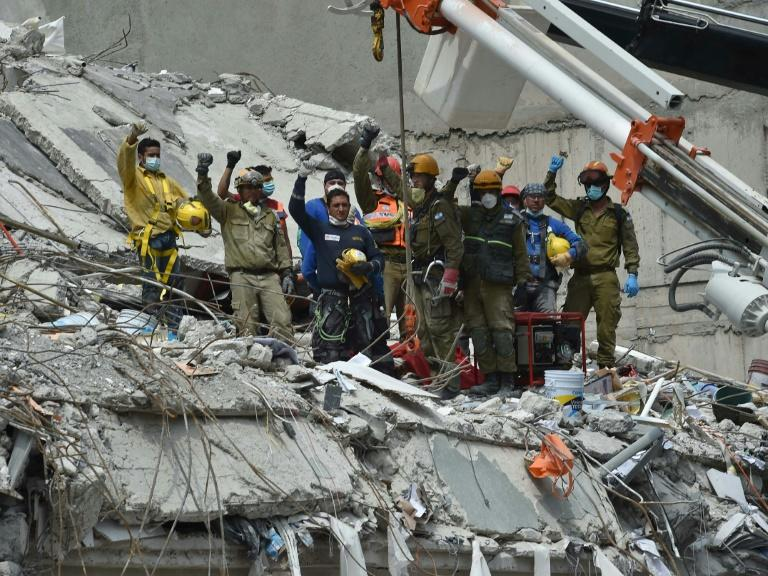 Rescuers call for silence during the search for survivors in a flattened building in Mexico City