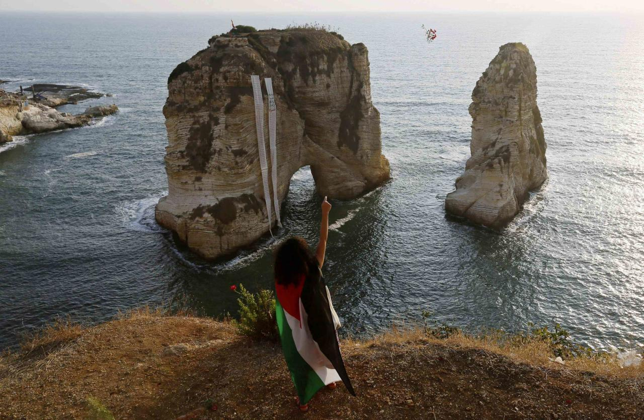 A protester wearing a Palestinian flag throws flowers into the Mediterranean sea during a demonstration against Israel's military action in Gaza, at Rawshe rock in Beirut July 22, 2014. Israel pounded targets across the Gaza Strip on Tuesday, saying no ceasefire was near as top U.S. and United Nations diplomats pursued talks on halting the fighting that has claimed more than 600 lives. Hamas, the dominant group in the Gaza Strip, and its allies fired more rockets into Israel, triggering sirens in Tel Aviv. One hit a town on the fringes of Ben-Gurion International Airport, lightly injuring two people, officials said. Banners with the names of Palestinians killed in Gaza, hung up by the protesters, are seen on Rawshe rock. REUTERS/Jamal Saidi (LEBANON - Tags: CIVIL UNREST POLITICS TPX IMAGES OF THE DAY)