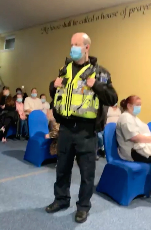 A police officer stands among the congregation at the church in Cardiff, Wales. (Wales News Service)