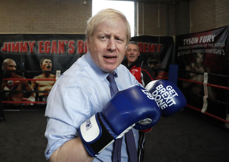 Britain's Prime Minister Boris Johnson dons some boxing gloves for a 'sparring session' during a stop in his General Election Campaign trail at Jimmy Egan's Boxing Academy in Manchester, England, Tuesday, Nov. 19, 2019. Britain goes to the polls on Dec.12. (AP Photo/Frank Augstein)