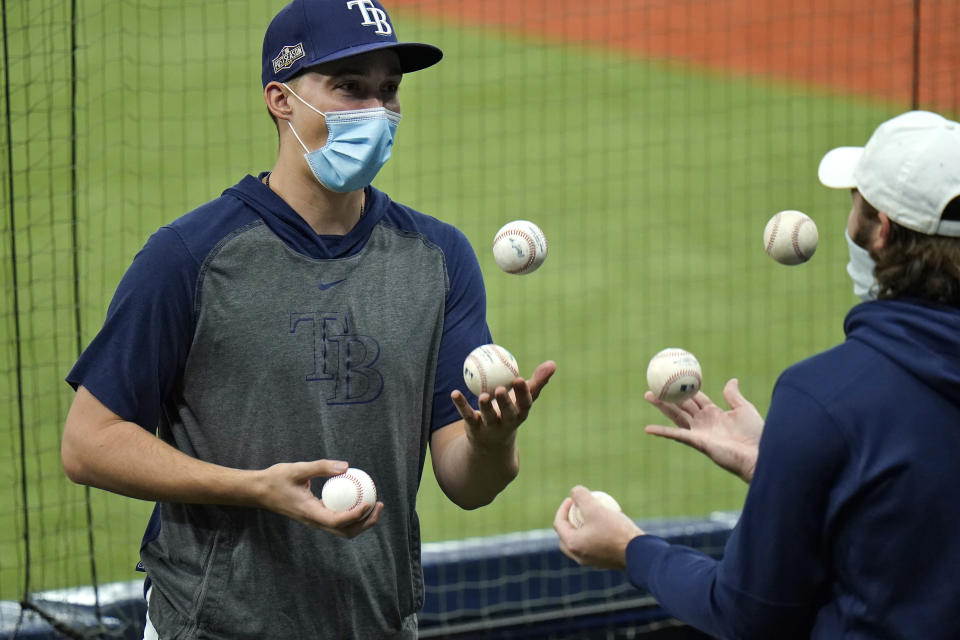 Tampa Bay Rays pitcher Blake Snell, left, juggles baseballs with a teammate during the seventh inning of Game 2 of an American League wild-card baseball series against the Toronto Blue Jays Wednesday, Sept. 30, 2020, in St. Petersburg, Fla. (AP Photo/Chris O'Meara)